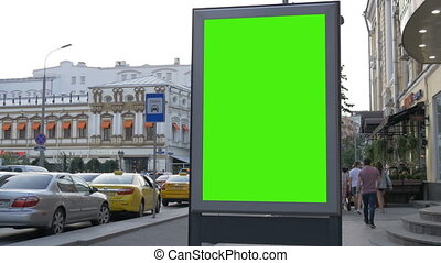 A Billboard with a Green Screen on a Busy Street.