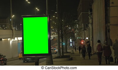 A Billboard with a Green Screen on a Busy Street. People walk along the sidewalk,