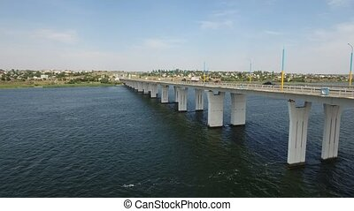 A bird`s eye shot of a high and long bridge with lampposts over the Dnipro