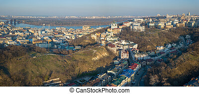 A bird's eye view, aerial panoramic view from drone to the Podol district, oldest historical center of Kiev, the Dnieper River and the left bank of Dnieper in the city of Kiev, Ukraine.