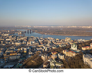 A bird's eye view, aerial view shooting from drone of the Podol district, oldest historical center of Kiev, the Dnieper River and the left bank of Dnieper in the city of Kiev, Ukraine.