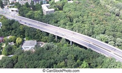 A bird's eye view of cars are moving through the forest on the bridge in the summer.