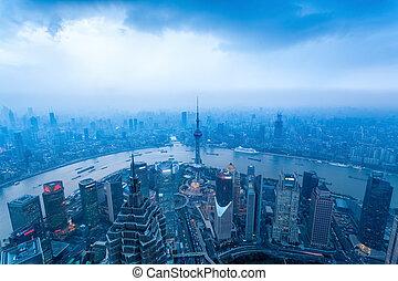 a bird's eye view of shanghai at dusk with cloudy sky