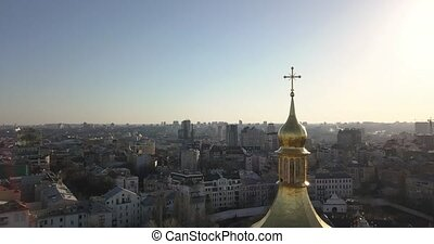 A bird's eye view, panoramic video from the drone in 4K to the the golden dome of Saint Sophia's Cathedral in the city of Kiev, Ukraine against a bright sun.