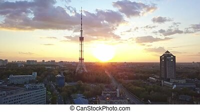 A bird's eye view video from the drone in 4K to the Kyiv TV Tower and Kyiv TV Center in the city Kiev, Ukraine. Pedestal up slow video against a bright sun, at summer.