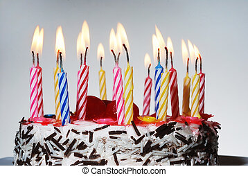a birthday cake with lighted candles