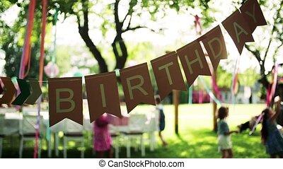 A birthday party of children outdoors in garden in summer, ...