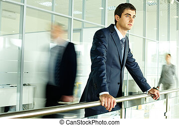 A bit of rest - Businessman standing by banisters with ...