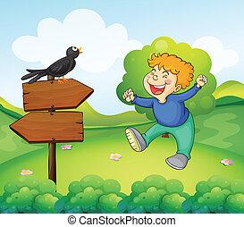 A black bird above the wooden sign near a young boy