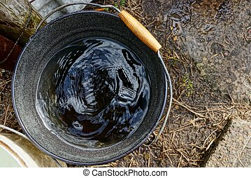 a black bucket full of water is standing on the street