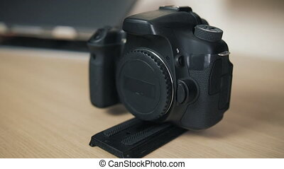 A black camera without a lens with a quick detachable plate is on a wooden table.