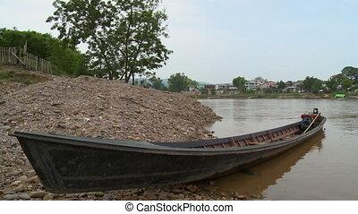 A close up shot of a black canoe docked at a riverbank