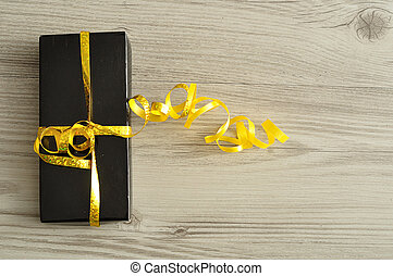 A black gift box decorated with a golden ribbon isolated on a wooden background