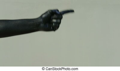 A black hand on a light wall shows a pantomime with an index finger