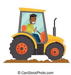 A black happy farmer in tractor on a rural farm field.
