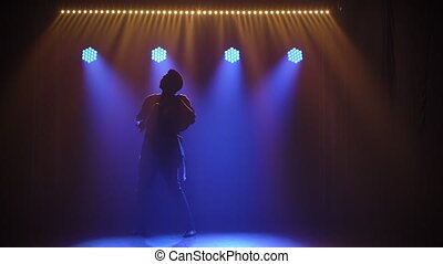 A black man bangs on an african talking drum yuka and dances to the beat of the music against a backdrop of blue spotlights and smoke. Silhouette. Musical instruments world culture sound. Slow motion.