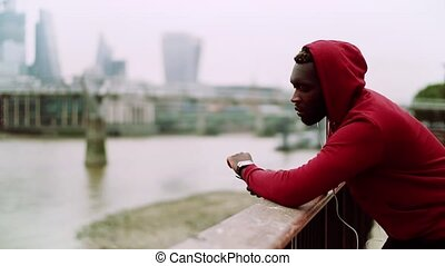 A black man runner with earphones and hood on his head in a...