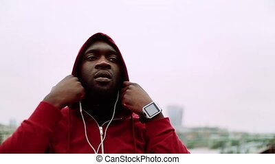A black man runner with earphones putting a hood on his head...