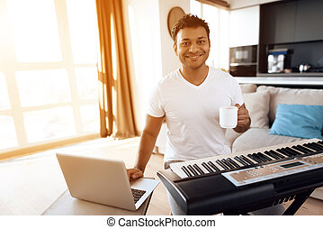 A black man sits in the living room of his apartment and plays a synthesizer. He composes music and drinks coffee.