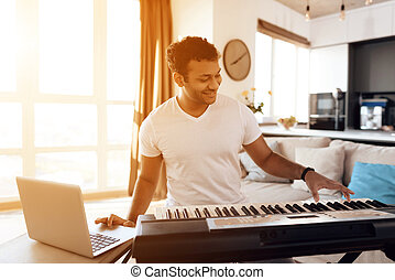 A black man sits in the living room of his apartment and plays a synthesizer. He composes music.
