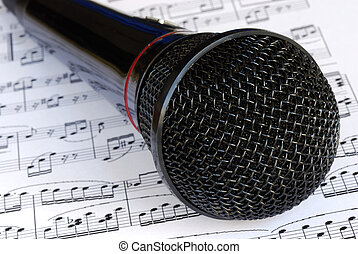 A black microphone on the top of music sheets