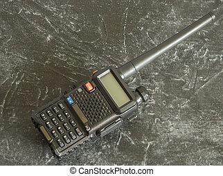 A black portable radio station on a dark concrete background