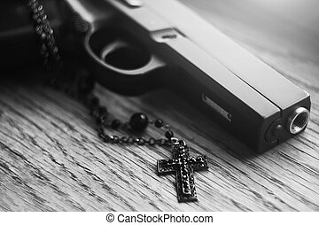 A black-white image of a gun that lies along with a black Catholic cross