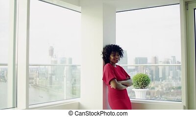 A black woman standing by the window against London panorama.