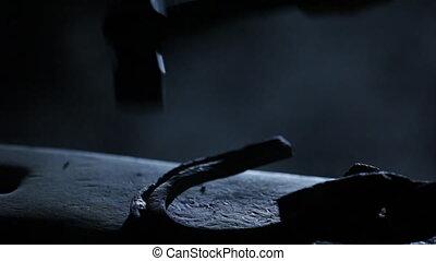A blacksmith hitting a metal - A medium shot of a blacksmith...