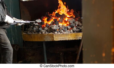 A blacksmith inverts the red-hot metal parts in the furnace...