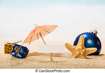 A blank card on peg, an umbrella, Christmas ball and gifts, starfish in the sand against the background of the sea.