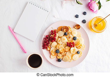 A blank notebook for your text. Tiny pancakes with berries. Breakfast concept, food trends, life style. Copy space