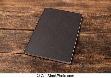 A blank notebook page and pen on wood office table. Top view with copy space.
