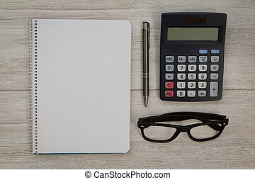 A blank notebook with a pencil and a calculator