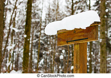 blank sign with arrow and snow in the forest