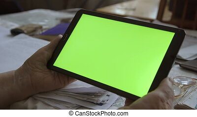 A blank tablet PC in landscape orientation with a green screenin hands.