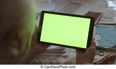 A blank tablet PC in landscape orientation with a green screenin hands. 4k