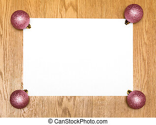 A blank white list with new year pink balls on wooden background