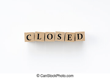A block of wood with closed letters on a white background
