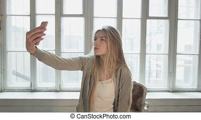 A blond blonde on the opposite window makes selfie using a smartphone. Beautiful young woman is shooting herself at the camera. Vintage interior.