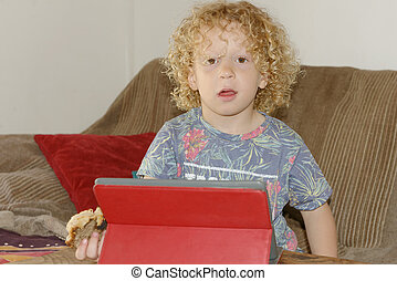 blond boy playing with a digital tablet