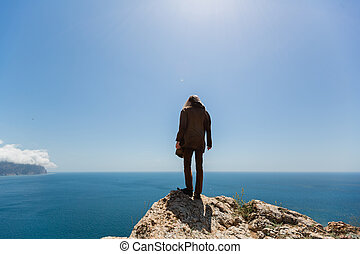 A blond man in a brown jacket on the edge of a cliff looks down curiously