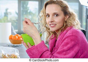 blond woman eating cereals, at morning