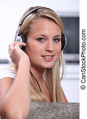 A blond woman looking at us with headphones on her head.