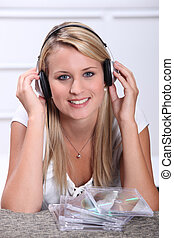 A blond woman, smiling at us, with CDs in front of her.