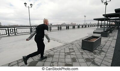 A blonde albino teenager tracer jumps street acrobatic...