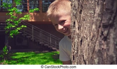 A blonde boy peeks out from behind a tree, playing hide and seek on a sunny summer day