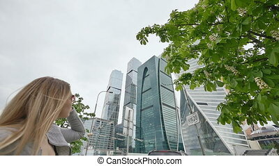 A blonde girl admires skyscrapers and high-rise buildings in the city center. Shooting in slow motion.
