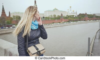 A blonde girl from the bridge sends an air kiss to motorists against the backdrop of the Kremlin. Moscow. Russia. Shooting in slow motion.
