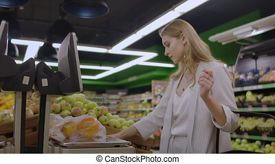 A blonde girl in a supermarket weighs oranges on an electronic scale pressing the display standing with a basket in her hands
